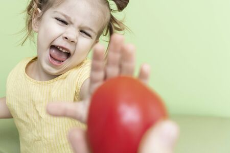 a little girl emotionally refuses the proposed tomato. children do not like vegetables, unbalanced nutrition of preschoolers Stock Photo