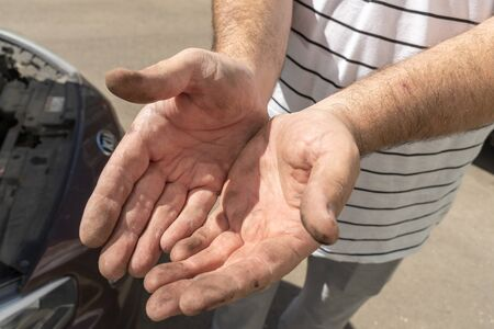 Auto mechanic works in the garage. Dirty hands in engine oil during repair