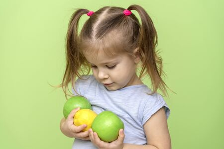 little girl 4 years old in a blue T-shirt on a green background holding a lemon and two apples in his hands, looking at it and smiling Stok Fotoğraf