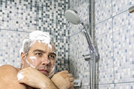 a big man in the foam stands in the bathroom, clasping himself with his hands and trembling from the cold, water does not pour. shutdown of water in water supply Banque d'images