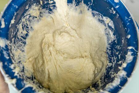 yeast dough mixed in a blue barrel. culinary background Archivio Fotografico