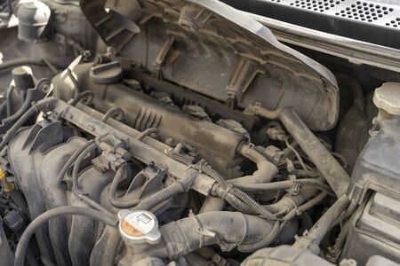 Auto mechanic works in the garage. Repair. Removing engine cover for oil change.