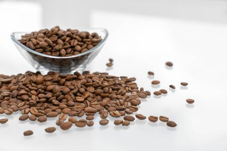 scattering of coffee beans on a glossy bright table with reflection. a bowl with grains in the background. breakfast concept