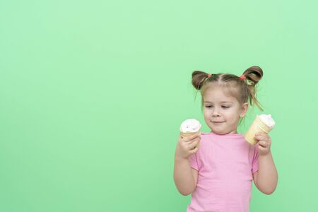 little girl 4 years old in a pink T-shirt on a green background holding an ice cream in his hands and looking at it with anticipation, a mockup with space for text Stok Fotoğraf