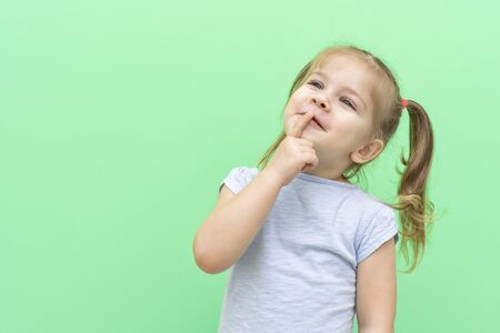 little nice girl 4 years old in a blue T-shirt on a green background in a blue T-shirt emotionally thought, index finger near lips. space for text on the left