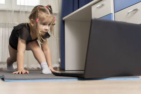 the child does gymnastics on a gymnastic rug at home in front of a computer. distance learning sports