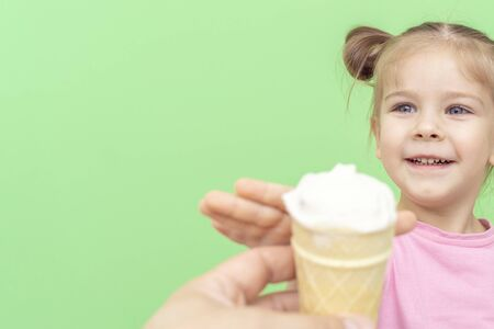 little girl 4 years old in a pink T-shirt on a green background smiles and reaches out to ice cream in a waffle cup, space for text on the left
