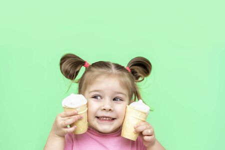 little girl 4 years old in a pink T-shirt on a green background smiles and puts 2 cups of ice cream on her cheek. negative space