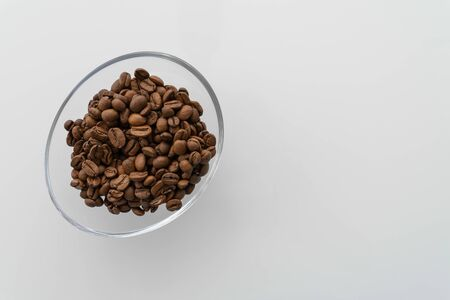 Coffee beans in a glass bowl on a glossy light table. view from above Standard-Bild