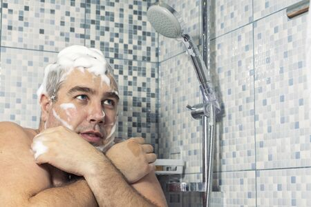 a man of 30-40 years old in a foam stands in the bathroom, clutching himself with his hands and trembling from the cold, water does not pour. water supply failure
