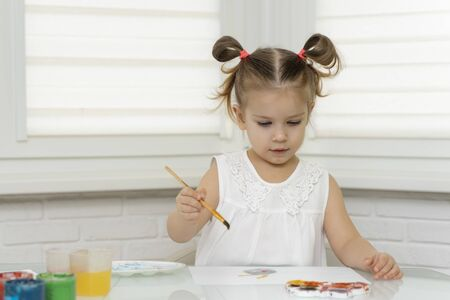 Girl draws paints in self-isolation in quarantine, reaches for paints with a brush