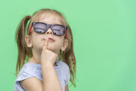 little girl 4 years old in a blue T-shirt on a green background in blue t-shirt and sunglasses emotionally posing, copy space