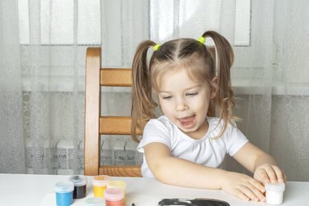 girl laughs  and opens a can of white paint. children's creativity during the period of self-isolation and quarantine in connection with the coronavirus. focus on the baby's hand