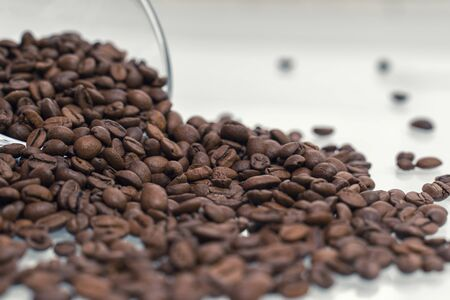 Coffee beans pour out of a glass bowl onto a light surface. coffee background, close-up, selective focus