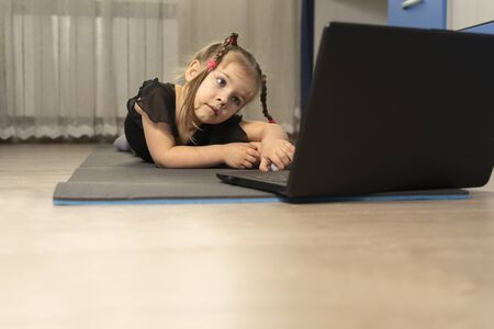 a little girl in a black gymnastics leotard is doing gymnastics at home online in front of a laptop. space for text and copy space. Stok Fotoğraf
