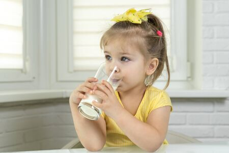 4 years old girl in a yellow blouse drinks milk from a glass in the kitchen