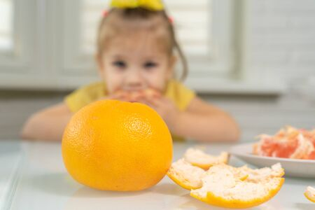 3-5 years old little girl in a yellow blouse eats grapefruit. the importance of citrus in children's nutrition Stok Fotoğraf