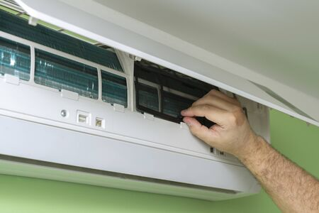 Male technician repairing and reading air conditioners. Opening the cover and cleaning the right filter Imagens
