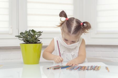little girl in a disposable mask draws with crayons at the table. self-isolation of the house in the fight against caronavirus
