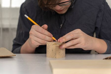a teenager in a work coat sits at a desk draws a drawing on a box for cutting wood. activities at home during the period of quarantine and self-isolation