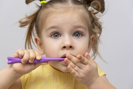 little girl in a yellow shirt is brushing her clean teeth and covers her mouth with her hand. emotional with scared eyes. problems with teeth and gums in children Banque d'images