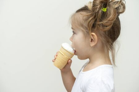 3-4 years old girl in a white t-shirt eating ice cream. profile view and copy space