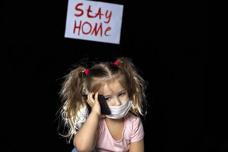 little girl talking on the phone on a black background and talking on a smartphone in a mask. children miss chatting with friends and relatives. quarantine and self-isolation. Backdrop poster with red letters stay home. a call Imagens