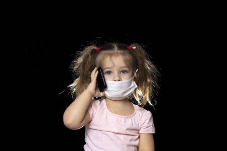 little girl talking on the phone on a black background and talking on a smartphone in a mask. children miss chatting with friends and relatives. quarantine and self-isolation