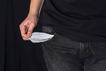 A concept without money. A man shows empty pockets. no money for karate and self-isolation. a man stands on a black background and holds an empty pocket in his right hand Stock Photo