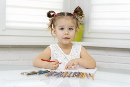 Little girl 4 years old in a disposable mask draws with pencils at home at the table. children's creativity on self-isolation at home