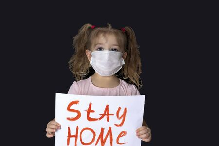 A little girl in a medical mask stands with a banner to stay home. A call to stay at home. holding a poster in front of him. quarantine. self-isolation Imagens