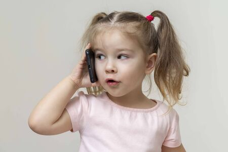 little girl talking by phone outdoor. The concept of addiction of children and gadgets.Using the gadget, bad habits of the younger generation, parental control, protecting children on the Internet, restricting content and access concept