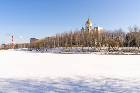 cityscape in winter. frozen lake with traces of ducks, an Orthodox church, pipes of a plant
