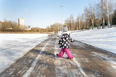 3-4 years old child walks along the wide embankment of a frozen pond in winter on a sunny day 版權商用圖片