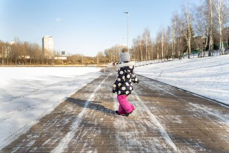 3-4 years old child walks along the wide embankment of a frozen pond in winter on a sunny day Imagens