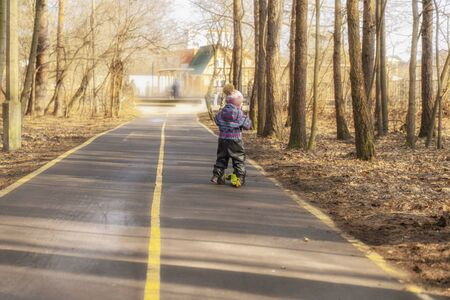 a child races on a scooter along an asphalt road in a spring park