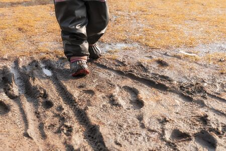 child's feet in rubber boots stained in spring mud