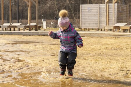 3-4 years old girl in a hat and overalls jumping fun in a big dirty pool Archivio Fotografico