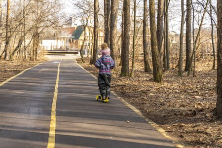 the child races on a scooter along an asphalt road through a spring park from the viewer. backlight Фото со стока