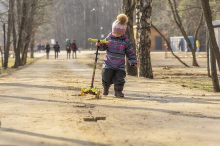 3-4 year old child in a hat and overalls walks along a dirt road in a city park and drags a scooter