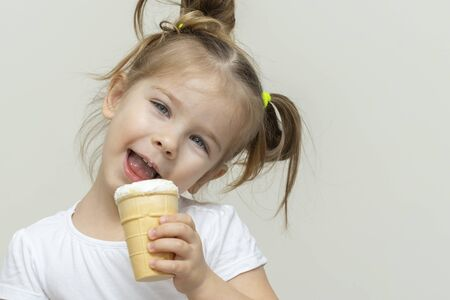 3-4 years old girl in a white t-shirt eating ice cream and smiling. happy face and laugh