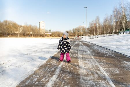 3-4 years old child walks along the wide embankment of a frozen pond in winter on a sunny day Banco de Imagens