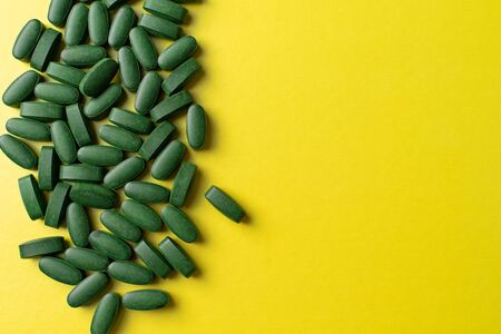 green pills chlorella on a yellow background. nutritional supplements for a healthy diet
