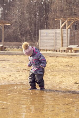 3-4 year old child in a hat and overalls enters a large dirty pool