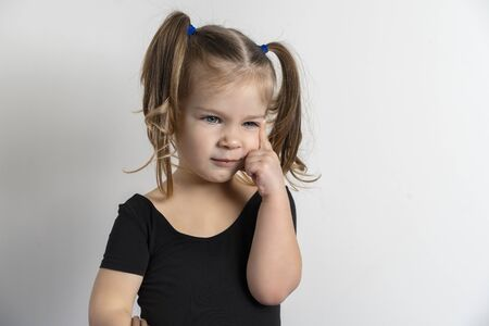 little european girl on a light background with a dreamy facial expression. hand in the face in a pensive pose