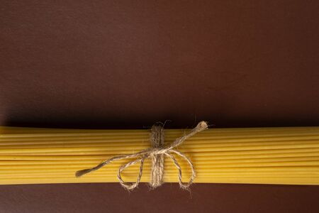 spaghetti on a brown background, tied with a rope,