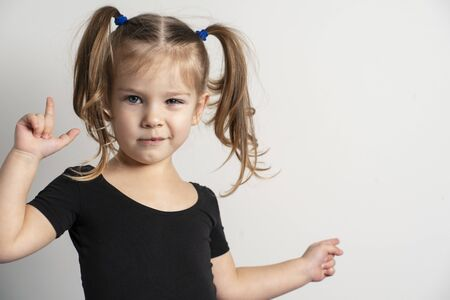 portret emotional 4 year old girl with two ponytails. one hand shows on copy space to the right of itself, the other is emotionally raised up Stock Photo