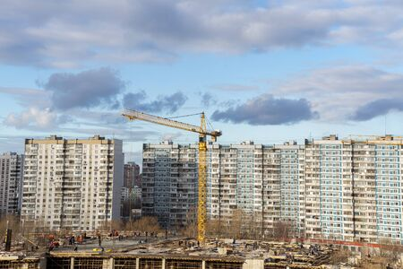 high view of a residential quarter of a metropolis with a building with a beautiful sky with clouds and a construction crane