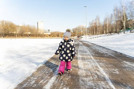 3-4 years old child walks along the wide embankment of a frozen pond in winter on a sunny day Standard-Bild
