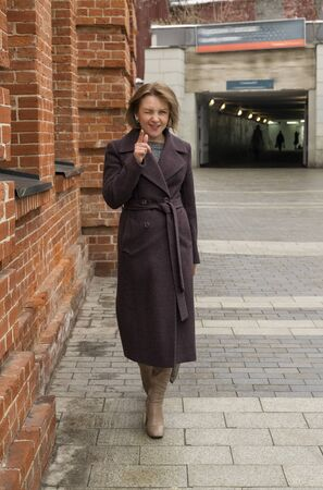 beautiful woman 30-40 years old in a long coat and high heel boots walks along a city street past the red wall and smiles, hand forward, eyes narrowed Imagens - 147911210